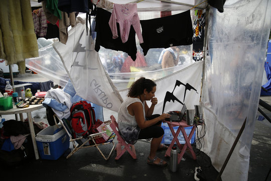 An Argentinian fan uses her computer outside her motorhome as she passes time amongst others before Sunday's World Cup final between Argentina and Germany at the Terreirao do Samba in Rio de Janeiro