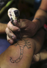 A man gets a tattoo of a scorpion on his arm in Mostorod, east of Cairo