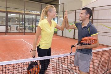 happy couple playing tennis indoor tennis court