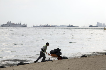 A worker cleans up oil and other debris from a beach in Singapore
