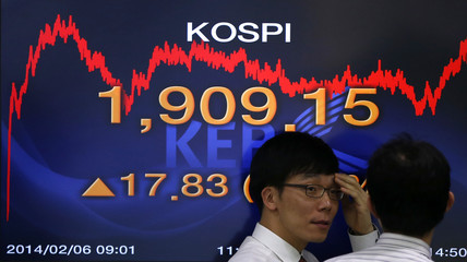 Currency dealers talk in front of an electronics board showing the KOSPI at a dealing room of a bank in Seoul