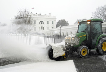 A snow blower clears snow from a driveway around the White House in Washington