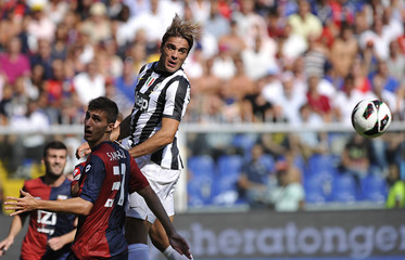 Juventus'  Matri and Genoa's Sampirisi jump for the ball during their Serie A soccer match at the Ferraris stadium in Genoa