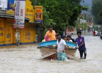 Villagers pull a boat with people after rescuing them, on a flooded road in Biyagama