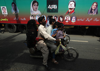 A family on a bike rides past a truck with pictures of Imran Khan, chairman of Pakistan Tehreek-e-Insaf (PTI) political party, and other party leaders, outside his residence before the start of today's Freedom March in Lahore
