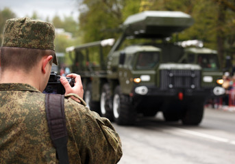 Army journalist photographer. Soldier takes picture military vehicle