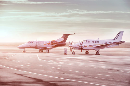 Private jet planes parking at the airport. Private airplanes at sunset,