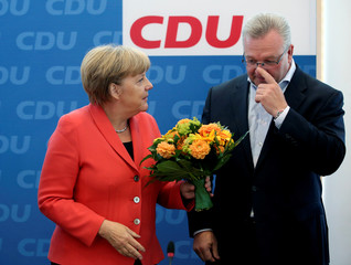 German Chancellor and chairwomen of the CDU Merkel hands over a bunch of flowers to top candidate for the Berlin city-state elections Henkel in Berlin