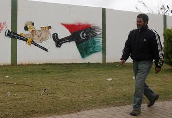 A man walks past a cartoon graffiti depicting Libyan leader Muammar Gaddafi on the fence of a military base in Benghazi