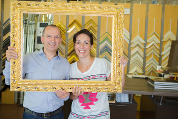 Portrait of man and woman looking through a picture frame