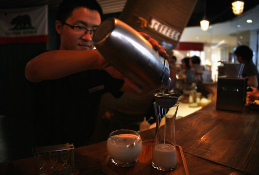 A waiter at a newly opened specialist coffee shop pours an iced-coffee drink for the members of a cupping (tasting) class in Beijing