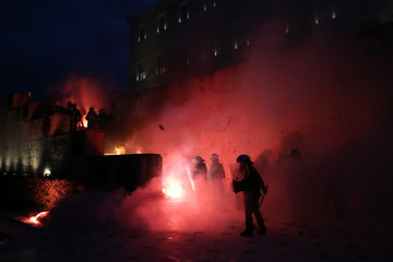 Riot police stand among flare smoke on the Tomb of the Unknown Soldier burns during clashes outside the parliament building as Greek lawmakers vote on the latest round of austerity Greece has agreed with its lenders, in Athens