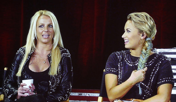 """Judges from the reality series """"The X Factor"""" Spears and Lovato are pictured on a video screen via satellite from Miami at the Fox  television network portion of the Television Critics Association Summer press tour in Beverly Hills"""