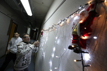A man prepares Christmas lights in the corridor of an occupied building in Rome