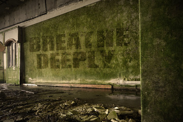 text breathe deeply on the dirty wall in an abandoned ruined house