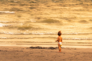 Baby in diapers are looking at the sea skeptically on the beach in the evening, the concept of learning.