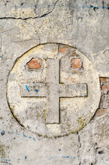 Cross symbol on a old, ruined wall