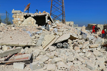 Civil defence and Syrian Arab Red Crescent members work at a site hit by an airstrike at an industrial area of rebel-held Idlib city