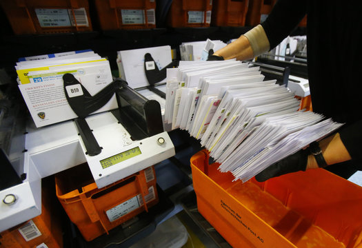 A worker collects mail from a letter sorting machine at Austrian Post logistics centre in Vienna