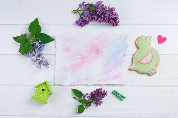 Empty paper card decorated with lilac flowers on white wooden background