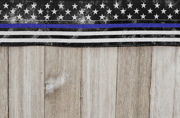 Thin blue line USA old flag on a weathered wood background