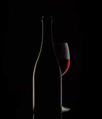 silhouette of a wine bottle and glass on black background