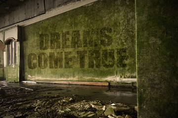 text dreams come true on the dirty wall in an abandoned ruined house