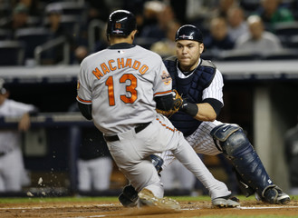 Orioles' Machado is put out at home plate by Yankees catcher Martin on a fielders choice during the third inning in Game 4 of their MLB ALDS baseball playoff series in New York