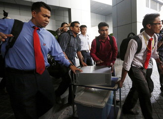 Malaysian plainclothes police remove a hard drive and a box labelled laptops from the offices of troubled state investment fund 1MDB in Kuala Lumpur