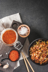 Asian cuisine. Fermented food. Traditional Korean dish: kimchi cabbage - sauerkraut with traditional kimchi sauce from hot red chili pepper, garlic, spices, salt. On a black stone table. Copy space