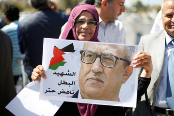 Woman holds a picture of Jordanian writer Nahed Hattar, who was shot dead, during a sit-in in front of the prime minister's building in Amman
