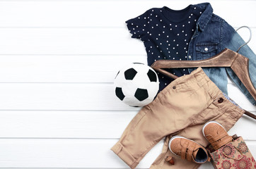 Baby boy clothing set (blue t-shirt with white stars, jeans shirt, brown shoes, pant). Wish list or shopping overview for pregnancy and baby shower. View from above.