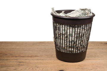 Garbage basket full of crumpled dollars stands on an old wooden table isolated on a white background
