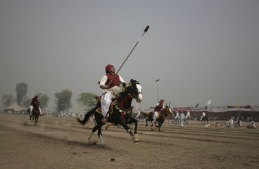 Horse-riders patricipates in tent-pegging competition during three-day horse and cattle show in Faisalabad