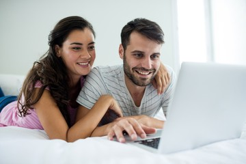 Couple using laptop in the bedroom