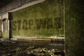 text stop war on the dirty wall in an abandoned ruined house