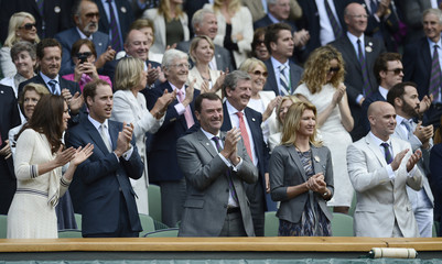 Britain's Prince William and his wife Catherine, Duchess of Cambridge applaud on Centre Court after Roger Federer of Switzerland defeated Mikhail Youzhny of Russia in their men's quarter-final tennis match at the Wimbledon tennis championships in London