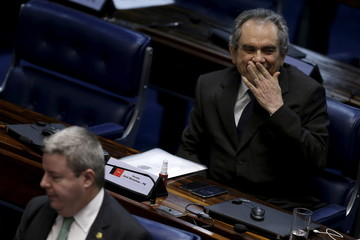 Senator Lira gestures near Senator Anastasia during a senate session to elect members for a special committee, which will organise impeachment procedures against President Rousseff, in Brasilia
