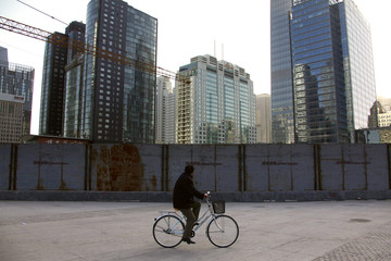 A man looks up at new buildings and others that are still under construction as he rides his bicycle in central Beijing