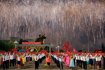 Fireworks explode over participants in a mass dance in the capital's main ceremonial square, a day after the ruling Workers' Party of Korea party wrapped up its first congress in 36 years, in Pyongyang