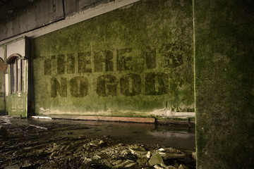 text there is no god on the dirty wall in an abandoned ruined house