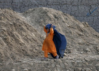 Afghan girl wears a burqa for fun as she walks along a road in Kabul, Afghanistan
