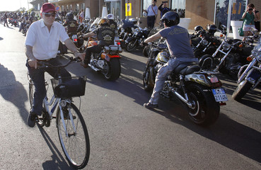 A man rides a bicycle as Harley-Davidson bikers arrive for the European celebration of its 110th anniversary in Ostia near Rome