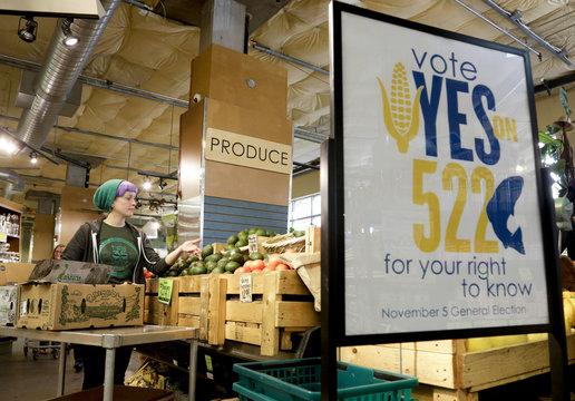 An employee stocks produce near a sign supporting a ballot initiative in Washington state that would require labeling of foods containing genetically modified crops at the Central Co-op in Seattle, Washington