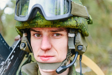 Portrait of a Russian soldier in modern military uniforms and weapons, machine gun. Green form on the background of a pine forest