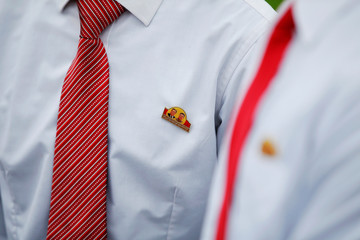 Schoolchildren wear badges with pictures of former North Korean leaders Kim Il Sung and Kim Jong Il near April 25 House of Culture, the venue of Workers' Party of Korea (WPK) congress in Pyongyang