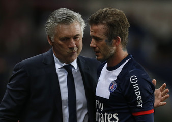 Paris Saint-Germain's Beckham is comforted by coach Ancelotti at the end of his team's French Ligue 1 soccer match against Brest at the Parc des Princes stadium in Paris
