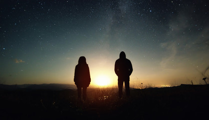 A couple of people man and woman stand at the sunset of the moon under the starry sky with bright stars and a milky way. Silhouetted photo against the starry night sky