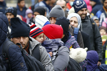 Migrants walk towards a makeshift camp in the village of Sentilj