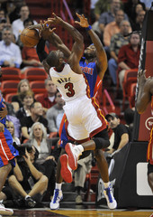 Heat shooting guard Wade has his shot blocked by Pistons center Wallace in the first period during their NBA preseason basketball game in Miami